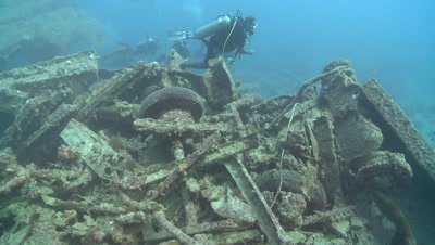 Divers over strewn military detritus, wreck of Thistlegorm, Antarctica