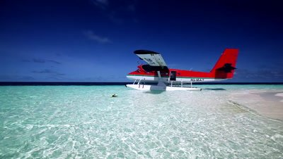 Airplane and woman snorkelling in the Maldives, Indian Ocean