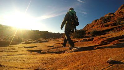 Man hiking over sandstone toward the sun in slow motion.