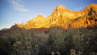Timelapse of sunset lighting up the cliff face in zion national park.