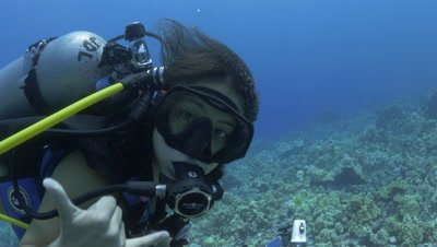 Female scuba diver looks with eyes and gives shocker off the Kona Coast of the Big Island Hawaii