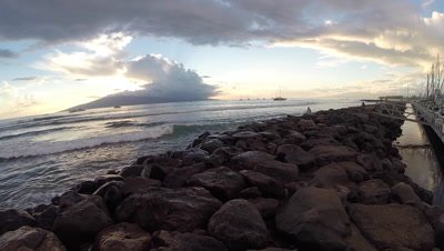 Aerial reveal of a surfer jetty and waves in Lahaina Harbor