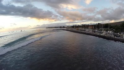Aerial from sunset with waves surfers and boats at Lahaina Harbor in Maui