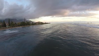 Aerial from sunset with waves surfers paddle board and boats at Lahaina Harbor in Maui