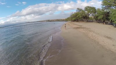 Aerial footage of a lady wading on Baby Beach in Lahaina Maui Hawaii
