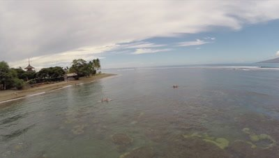 Aerial footage from of paddeling surfers over a coral reefs and beach at Baby Beach Lahaina Maui Hawaii