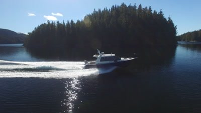 A speeding boat moving through the small isalnds in the Pacific Northwest region of Nimmo Bay in the Broughton Archipelago in Canada