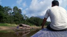 Traveling Down The Tahuayo River With The Guide Using A Paddle To Avoid Logs
