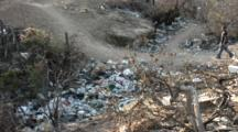 Dirt Road With Garbage In A Mexican Town, People Cross It