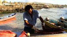 Fisherman Filets Fish On Dock  On Rapa Nui Island