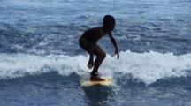 Local Indonesian Child Rides Wave In On Surfboard