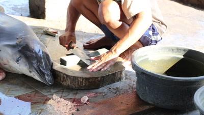 Medium shot of butcher sharpening knife at fish market