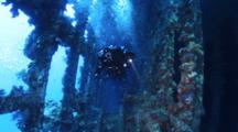 Divers Swim Through Wreck With Torch