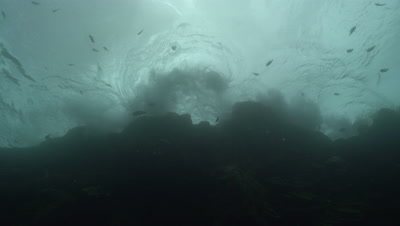 Looking up at waves over water surface under reef wall