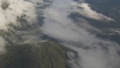High angle view of mountains and clouds below, pan and tilt left to mountains in distance, cam approaches mountains