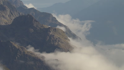 Travelling laterally over cloud covered mountains.