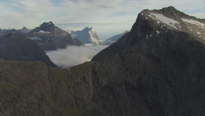 Cam flies over mountain top towards mountains and clouds in distance
