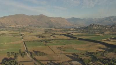 Flying over farmland at base of mountain range