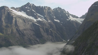 View of snowy mountains, pan left to cloud covered mountains