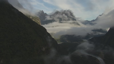 View of mountain and cloudy mountains in distance, camera moves behind mountain