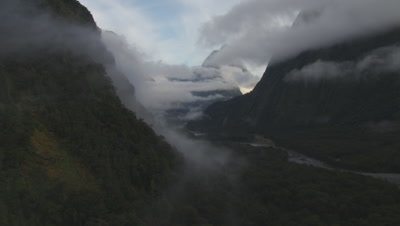 Flying through valley, cloud covered mountains in the background