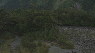 Flying over rocky stream in valley towards mountains