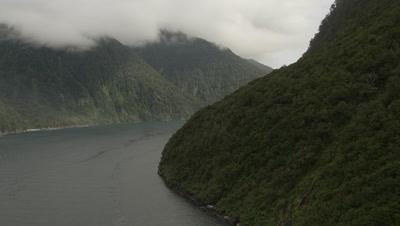 Fly around tree covered corner of coastline to reveal more scenery