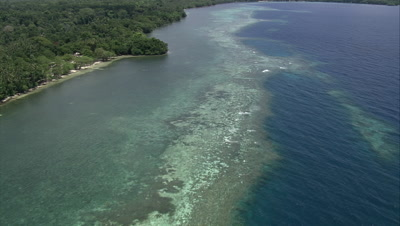 Flying along coast of island over shallow reef
