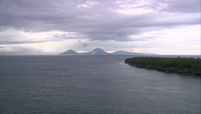 View of coast and mountain and volcano silhouettes in distance
