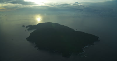 Very high aerial of Cocos Island at dawn, with sun's reflection on the ocean in the background
