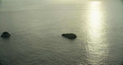 zooming in towards rock on ocean, reflected sun on water