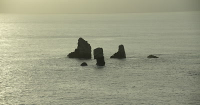 birds flying near rocks jutting out of water, sun reflecting off water