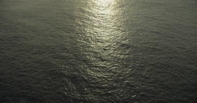 Travel over ocean, tilt up to reveal horizon. Sun reflecting off surface