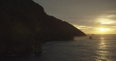 Flying along coast, waves crashing, silhouette of palm trees