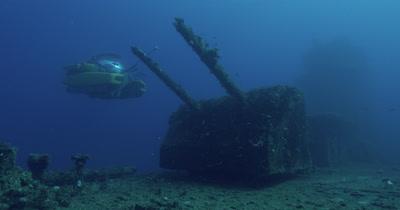 submarine surveying guns, ascending behind the wreck of USS Saratoga.
