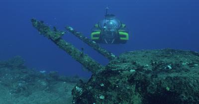 submarine in front of bridge of USS Saratoga. School of small fish crosses frame