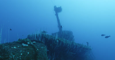 Pan left from bridge in distance to submarine by wreck of USS Lamson