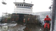 Crab Fishing Bering Sea - Fisherman Stacks Crab Pot On Rolling Icy Deck