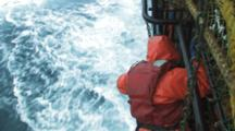 Crab Fishing Bering Sea Alaska - Fisherman Hangs Over Rail To Chain Down Stack