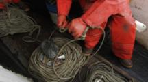 men on fishing boat work with lines, tie knots, longlining for halibut and black cod alaska