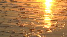 Sunset Reflected On Sand And Gentle Waves