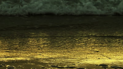 Close Up Gentle Waves Come Ashore During Golden Sunset