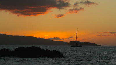 Silhouetted Sailboat And Sunset On Rugged Coast