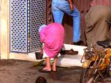 Old Woman Bent Over Sweeping Store Entrance