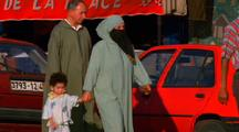 Woman And Children Hold Hands Down The Street, Morocco