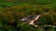 Car Junkyard Filled With Cars In Middle Of Forest - Aerial Over To Farm Buildings With Trees