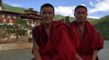 Pull Out To Three Men Posing For Camera In Red Robes