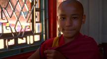 Young Lad, Monk In A Red And Yellow Robe Smiles For The Camera