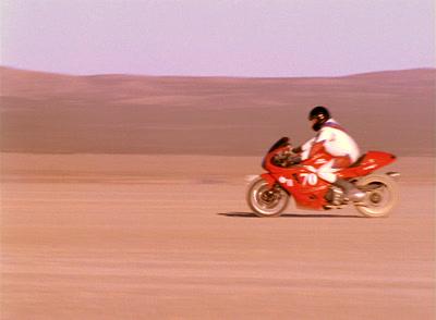 Man Rides Motorcycle In Desert