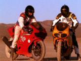 Two Men Ride Motorcycles In Desert